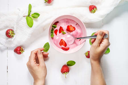 Strawberry ice cream in a pink bowl with strawberries on a concrete background. Female hand hold a spoon. Top view