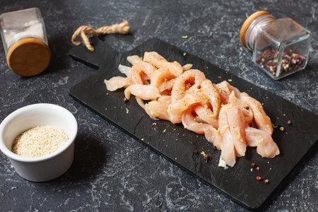fresh raw chicken cut in strips for a goulash or stir fry seasoned with spice rub heaped on a black stone background Foto de archivo