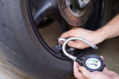 Man checking manually air pressure of motorcycle wheel before traveling. The air pressure is measuring in the bar unit.