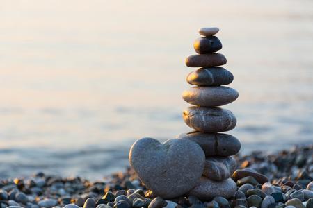 Grey stone in shape of heart in front of balanced stones on still water background Foto de archivo