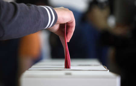 Older man voting at elections, hand putting ballot paper in ballot box. Banque d'images
