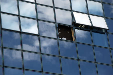 Reflection of the sky and clouds in windows, one broken, two opened Zdjęcie Seryjne