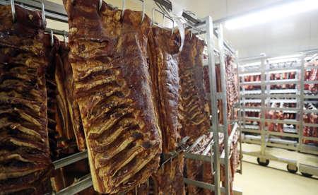 Piaces of meat, pork ribs hanging in big fridge