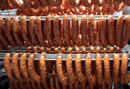 Piaces of meat, pork sausages hanging in big fridge