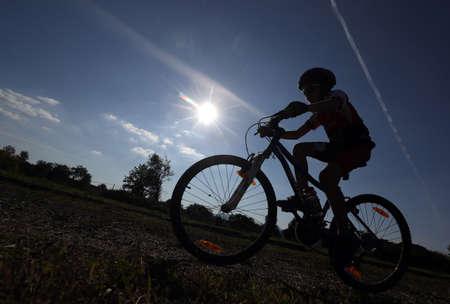 Silhouette of child riding bike Zdjęcie Seryjne