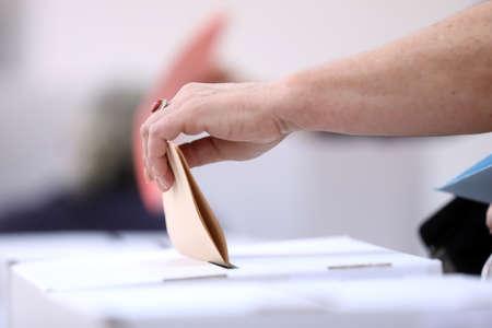 폴링 스테이션에서 지방 선거에 투표하면서 여자 핸드는 투표 용지를 던집니다. 손에 집중. 스톡 콘텐츠 - 78711139