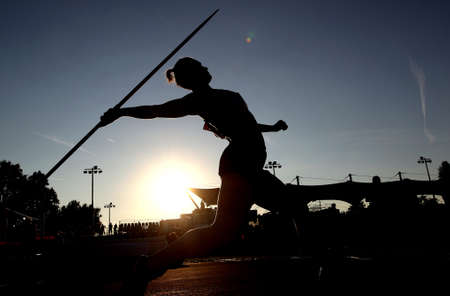 A woman silhouette throws a javelin during athletics competition