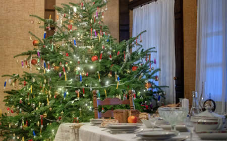 Decorated Christmas table with wheat, bread, candles, walnuts and Christmas tree behind
