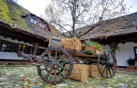Decorated Wooden chassis with gifts, Christmas lights and hay in front of old house