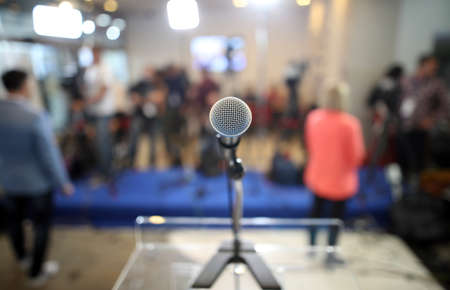 Microphone before start of politics press conference with journalist behind Zdjęcie Seryjne
