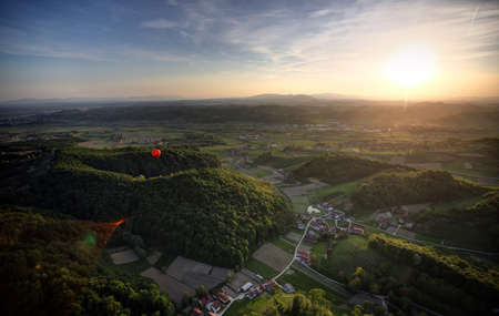 Hot Balloons in the air over forest and landscape in sunset.
