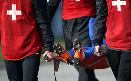 De medische staf vervoert de gewonde voetballer tijdens de voetbalwedstrijd op een brancard.