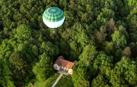 Hot Balloon in the air over forest, house and landscape in sunset.