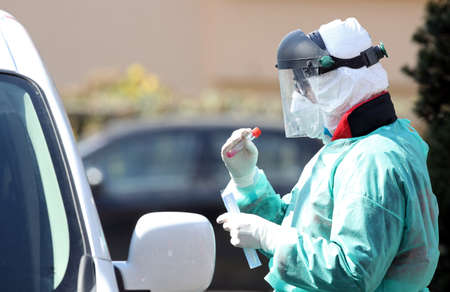 Medical staff member with mask and protective equipment performs Coronavirus nasal swabs test tubes at drive-through testing point in an effort to curb the spread of COVID-19 (novel coronavirus) Stockfoto