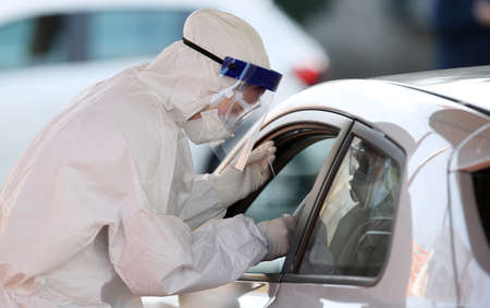 Medical staff member with mask and protective equipment performs fast antigen testing for SARS-CoV-2 (COVID-19, Coronavirus) nasal swabs test tubes at drive-through testing point.