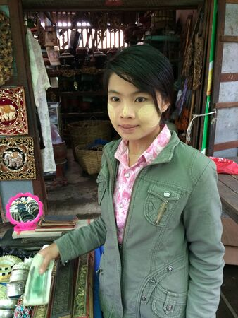 thanaka: Girl with thanaka in a market in Inle lake, Myanmar
