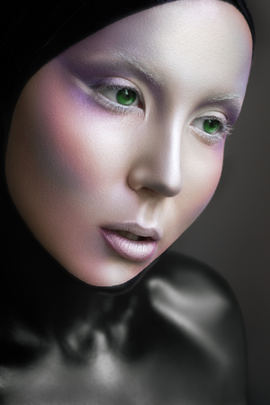 alien women: Mysterious space girl with silver airbrush make up and black colored body. Alien fashion look. Cold and magic.