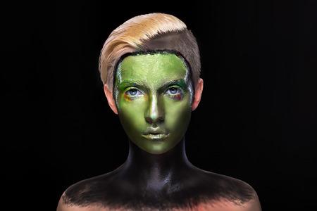 alien face: portrait of a woman with alien makeup, wet green paint all over her face, art makeup