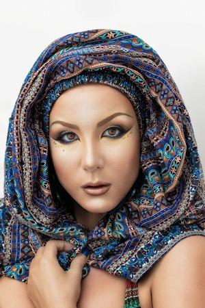 ojos azules: Retrato de una mujer hermosa con maquillaje �rabe de la moda, hecho en los colores azul y beige en paranja aislados sobre fondo blanco.