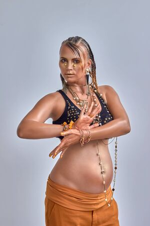 fingers on top: beautiful eight months pregnant woman, top and accessories, with art make up in golden color, dancing with hands, posing with fingers