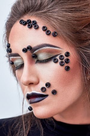 decollete: Fashion makeup with black beads on face, dark lips, close up portrait. Young beauty model with closed eyes, art make up. Creativity. Inspiration. Expressive Dramatic look.