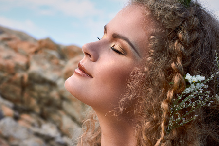 blue romance: Close up portrait of pretty girl in near rocks, closed eyes, curly hear with flowers, beautiful nature, sea view in summer Stock Photo
