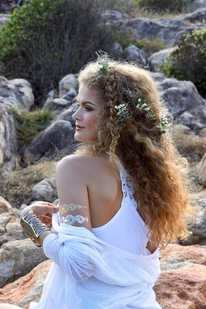 blue and white: young pretty girl in white dress with curly hear, near stones, pale rocks, beauty photography, romantic look