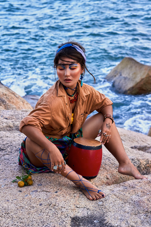 female shaman: Young woman shaman in bright clothes and makeup, with drum, seating in the mountain, sea view. Ethnic fashion photoshoot. Boho style. Stock Photo