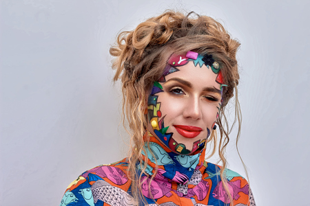 scrunchy: Close up portrait of young beautiful woman, model,  clown. Bright creative fantasy makeup, geometric shapes, circles. Multicolored paint, red, blue, orange, yellow, pink. Pop art style, avant garde.