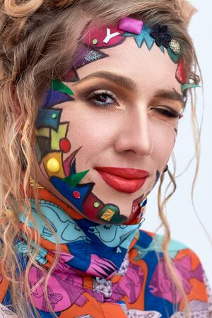 avant garde: Close up portrait of young beautiful woman, model,  clown. Bright creative fantasy makeup, geometric shapes, circles. Multicolored paint, red, blue, orange, yellow, pink. Pop art style, avant garde.
