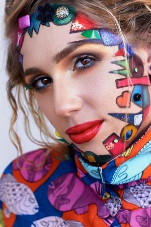 maquillaje de fantasia: Cerca de retrato de joven y bella mujer, modelo, payaso. Maquillaje brillante creativo fantas�a, formas geom�tricas, c�rculos. pintura multicolor, rojo, azul, naranja, amarillo, rosa. estilo del arte pop, de vanguardia.