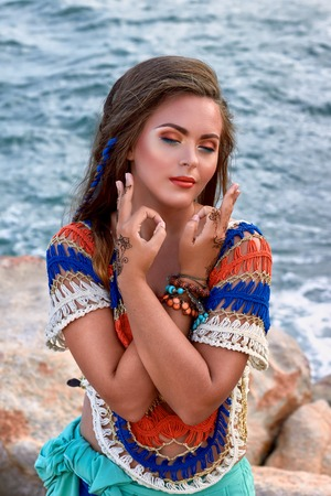 blue sea: ethnic fashion outdoor photo of beautiful sexy girl in bright clothes posing on summer ocean beach, sensual mood posing, boho style wear Stock Photo