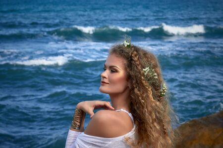 ojos azules: Retrato de la muchacha rizada sensual con flores en la cabeza, vestido de blanco, con vistas al mar, la naturaleza fotograf�a de belleza, verano viajan