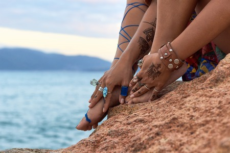 beautiful girls hands on feet with mehendi, accessorieson arms, relaxing moment, seating on mountain near sea Stock Photo