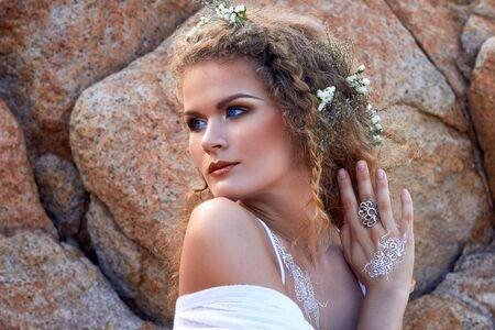 ojos azules: Retrato de la muchacha rizada sensual con flores en la cabeza, vestido de blanco en un jard�n de piedra cerca del mar, la naturaleza fotograf�a de belleza, los viajes de vacaciones de verano,