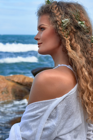 blue sea: portrait of pretty sensual curly girl with flowers in her head, white dress, in a stone garden near sea, nature beauty photography, summer traveling, vacation