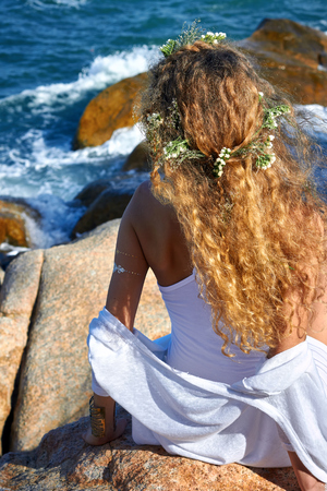 blue and white: portrait of pretty sensual curly girl with flowers in her head, white dress, seating in a stone garden near sea, nature beauty photography, summer traveling, vacation