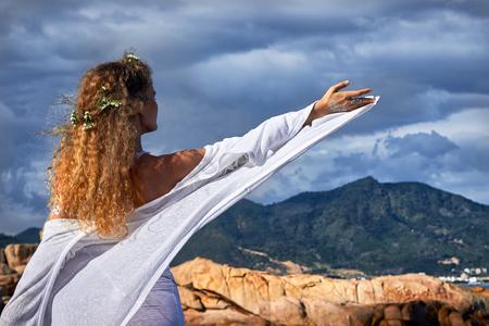 ojos azules: Retrato de la muchacha rizada sensual con flores en la cabeza, vestido de blanco, de pie en un jard�n de piedra cerca de la monta�a, belleza de la naturaleza fotograf�a, viajes, vacaciones de verano
