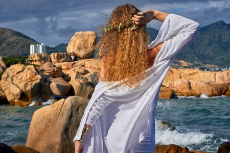 blue romance: portrait of pretty sensual curly girl with flowers in her head, white dress, standing in a stone garden near sea, nature beauty photography, summer traveling, vacation