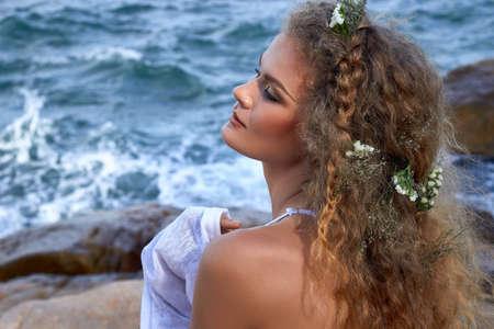 ojos azules: Retrato de la muchacha rizada sensual con flores en la cabeza, vestido de blanco, en un jard�n de piedra cerca del mar, la naturaleza fotograf�a de belleza, los viajes de verano, vacaciones