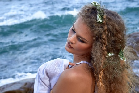blue and white: portrait of pretty sensual curly girl with flowers in her head, white dress, near sea, nature beauty photography, summer traveling, vacation Stock Photo