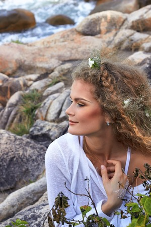 blue background: portrait of pretty sensual curly girl with flowers in her head, white dress, in a stone garden near sea, nature beauty photography, summer traveling, vacation