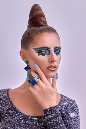 labios sensuales: Retrato de la hermosa joven, mujer, modelo. Fantas�a, brillante, maquillaje. Cubismo, estilo de pelo geometr�a. expresivas l�neas de colores azules, figuras, pendientes, anillos largos. Moda, mirada creativa. Foto de archivo