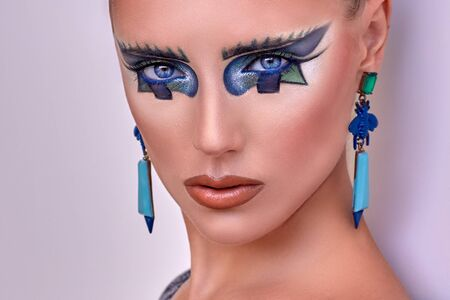 blue and white: Portrait of beautiful young girl, lady, woman, model. Fantasy, bright, stylish, makeup. Cubism, geometry style. Expressive  colored blue lines, figures, long earrings. Fashion, creative look.