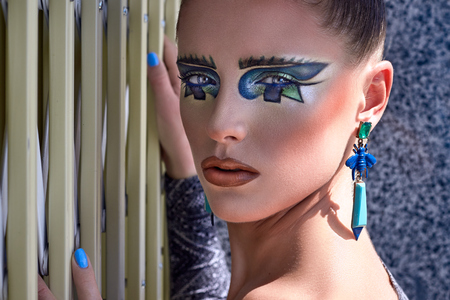 ojos azules: Portrait of beautiful young girl posing, lady, woman, model. Fantasy, bright, stylish, makeup. Cubism, geometry style. Expressive  colored blue lines, figures, long earrings. Fashion, creative look. Foto de archivo