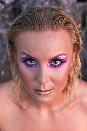 sexy glamour model: Portrait of beautiful woman with bright makeup in pink and purple colors in summer. Hair is wet, golden lips. Stones on background.