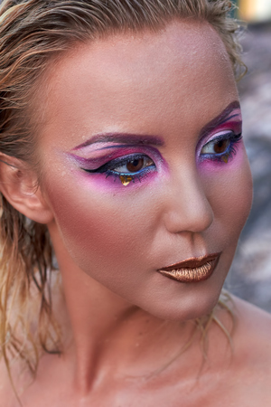 adult mermaid: Portrait of beautiful woman with bright makeup in pink and purple colors in summer. Hair is wet, golden lips. Stones on background.