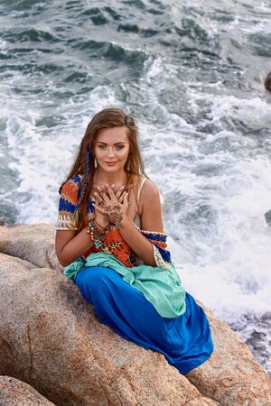 blue gold: ethnic fashion outdoor photo of beautiful sexy girl in bright clothes seating on summer sea beach, sensual relaxed mood , boho style wear