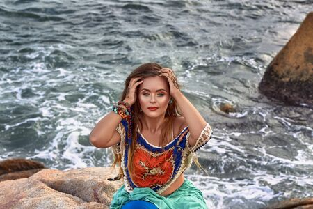 sexy pose: ethnic fashion outdoor photo of beautiful sexy girl in bright clothes seating on summer sea beach, sensual relaxed mood , boho style wear