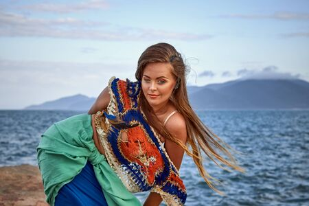 sexy girl posing: ethnic fashion outdoor photo of beautiful sexy girl in bright clothes posing on summer sea beach, sensual mood , boho style wear